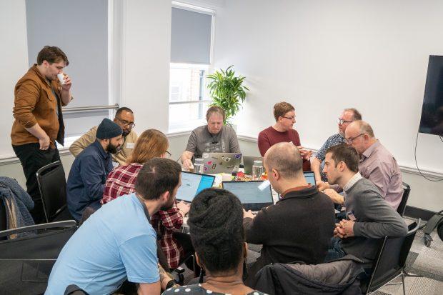 BPDTS employees talking through application features at a hackathon.