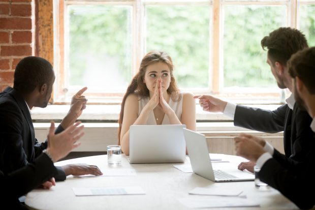 Perplexed young woman looking at coworkers pointing fingers at her.