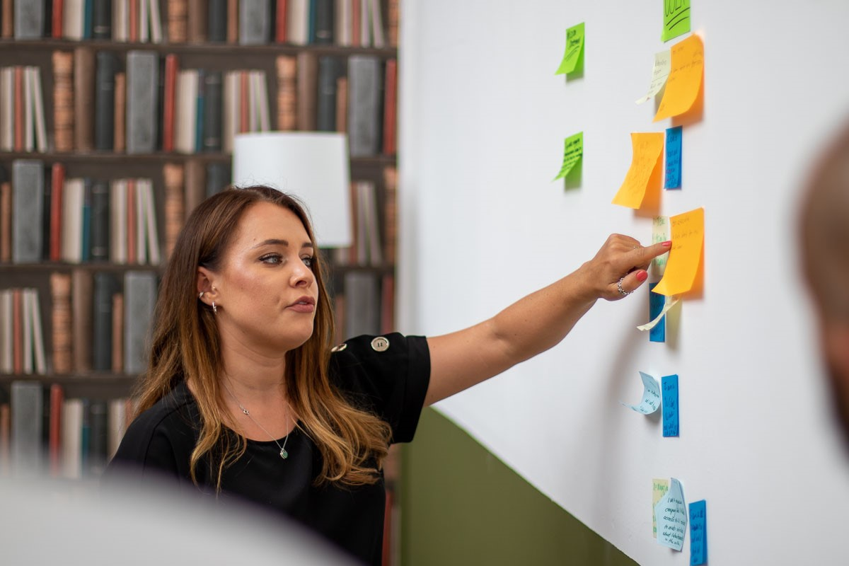 Jade Fryer, Senior Digital Performance Analyst, BPDTS pointing at post-it notes on a whiteboard.