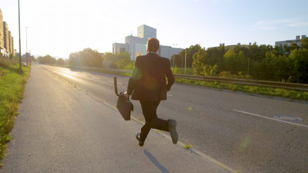 Young man wearing a suit running while holding a briefcase.